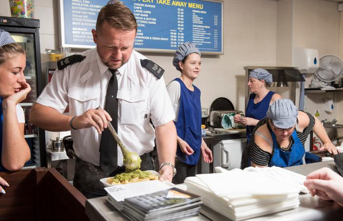 Police officer serving food in fish and chip shop